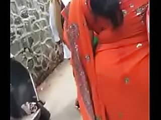 Desi orange saree aunty shaking her ass while boys at back cumming on her ass from back